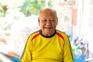Portrait of elderly asian man  is sitting smiling with yellow shirt at Sisaket province , Thailand.