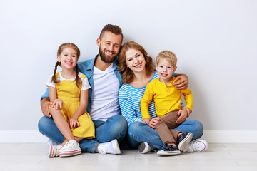 happy family mother father and children daughter and son  near an   grey blank wall.