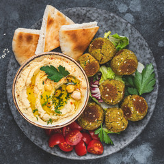 Hummus with falafel and pita bread on plate. Arabic cuisine appetizer. Top view, square composition