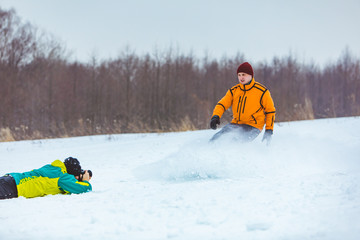 man laying on the ground and taking picture of snowboarder