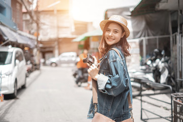 Smiling woman traveler in chiangmai market landmark chiangmai thailand holding camera with backpack on holiday, relaxation concept, travel concept