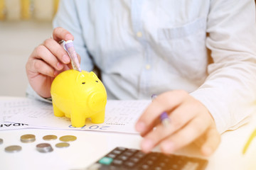 Picture of person depositing money in a yellow piggy bank. Isolated on background.