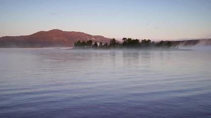 Fotomurales - A small island in a lake on a tranquil, foggy morning. Ottsjon, Sweden.
