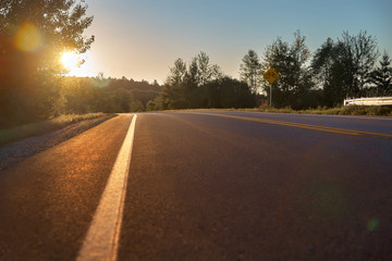 Road less traveled, low angle viewing, outdoor area. Sunset hours lighting the black paved road and mountains. Road goals to get somewhere.