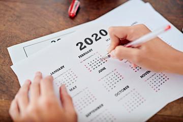 Crop businesswoman marking date on calendar
