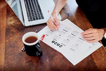 Unrecognizable freelancer making marks on calendar