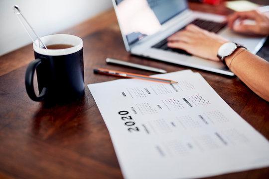 Calendar and tea near working freelancer