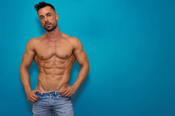 Fitness model man posing, wearing jeans and no shirt. There is a blue background