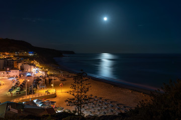 Night beach of the village of Salema, with the moon over the sea. Portugal.