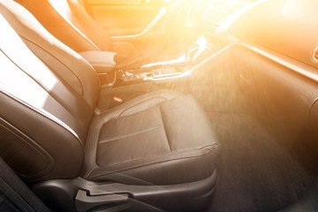 Close-up rear seat made of beige leather with a head restraint, in the background passenger seats with seat belts. Luxury car interior