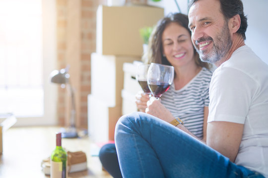 Middle age senior romantic couple in love sitting on the apartment floor with boxes around, celebrating drinking a glass of wine smiling happy for moving to a new home
