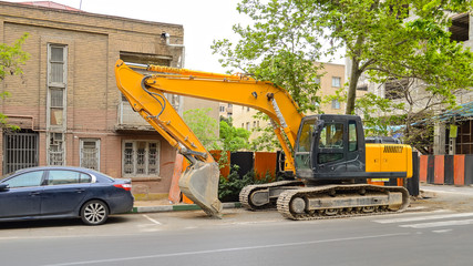 Hydraulic excavator parked on street in front of an old abandoned house, Tehran, Iran