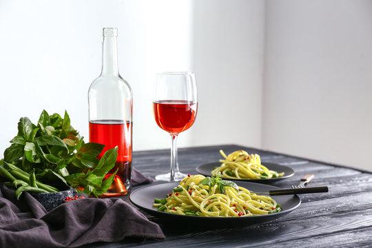 Tasty pasta with wine on dark table