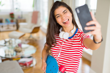 Beautiful skater woman smiling friendly standing with skateboard and taking a selfie using smartphone