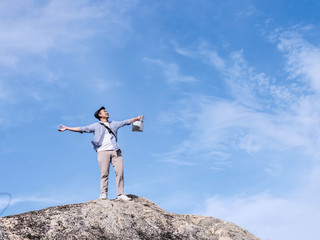 Asian tourist standing on the rock and raising hands with blue sky background,