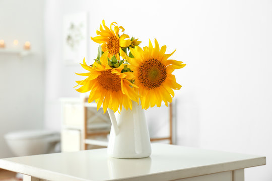 Beautiful sunflower flowers on table in bathroom