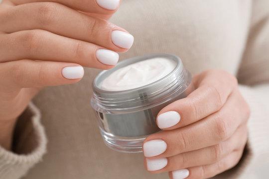 Woman with jar of cosmetic cream, closeup