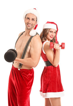 Young couple dressed as Santa Claus with dumbbells on white background