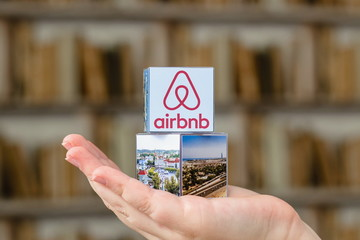 Minsk, Belarus - November, 2016: Travel around the world with Airbnb. Origami Paper  house. Logo Airbnb and globe.