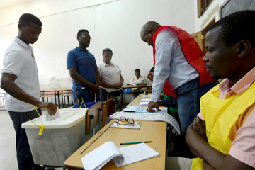 An official looks on as a man casts his vote during the presidential, legislative and provincial elections in Maputo