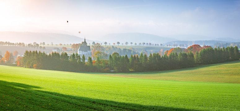 Herbstlandschaft mit Kirche auf dem Land