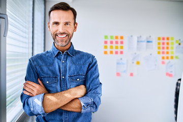 Portrait of handsome creative businessman looking at camera with arms crossed in office