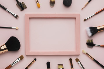 Flat lay arrangement with make-up brush and pink frame