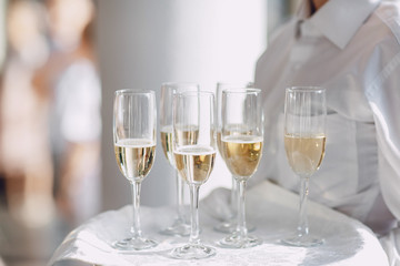 A waiter in a white shirt holds glasses of champagne on the tray