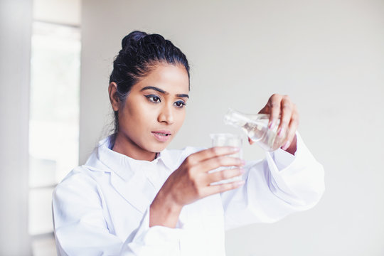 Young Indian biotechnology science student pouring water into a flask for a scientific experiment