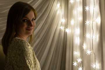 Portrait of a beautiful young white woman with brown hair in front of an illuminated star shaped christmas chain of lights