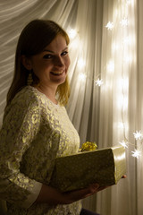 Portrait of a beautiful young white woman holding a christmas present in her hands in front of an illuminated star shaped christmas chain of lights