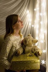 Portrait of a beautiful young white woman holding a teddy bear and a christmas present in her hands in front of an illuminated star shaped christmas chain of lights