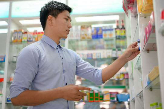 asian man going to buy medicine in pharmacy drug store, looking for medical treatment himself