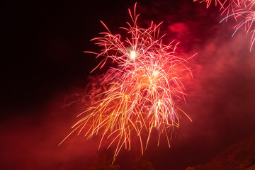 Red and orange fireworks against the backdrop of the night sky, Vittorio Veneto, Italy