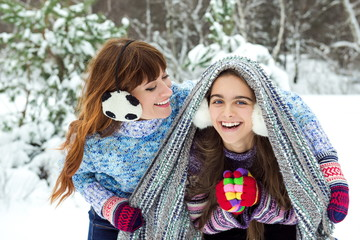 mother and daughter in winter. Two girls in the winter. clothes for the cold. Family together on snowy day. Winter holiday. Mom and her daughter spending weekend. Mom covers her daughter with blanket.