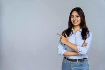 Confident smiling indian young woman professional student customer saleswoman looking at camera pointing at sales copy space isolated on grey studio background, happy lady showing aside portrait Fotomurales