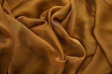 Photo sur Plexiglas Tissu Background from silk fabric. Golden silk fabric for sewing clothes. Textural background from a transparent silk fabric.