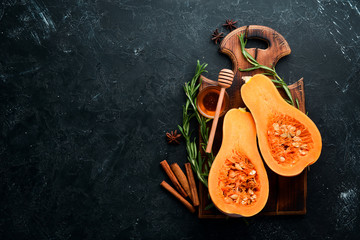 Fresh pumpkin with honey, healthy food. On a black stone background. Top view. Free copy space.