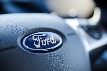 Ford sign on steering wheel close up.