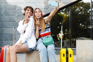 Photo of tourist women taking selfie photo with suitcases on city street