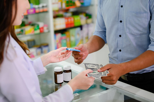 hands of selling pharmacist and man customers buyin medicine in drug store