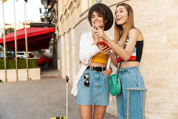 Photo of tourist girls using smartphone while walking on street