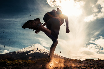 Young woman, trail running athlete runs on the trail with loose ground and volcano on the background