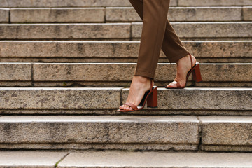 Business woman walking by steps outdoors in shoes.