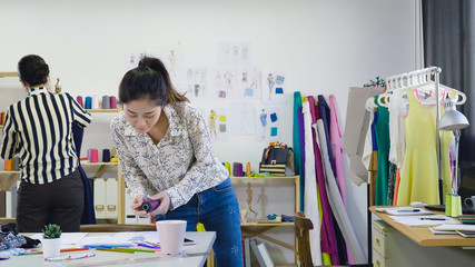 female seamstress holding thread in palm standing at table compare color of sketch paper. girl dressmaker doing last check before sewing. fashion designer colleague fixing tailor mannequin in studio