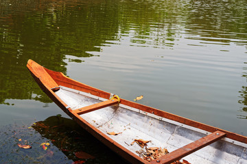 The front part of a boat in a lake, reflecting in the water. Some leaves are in the boat and floating on the water surface.