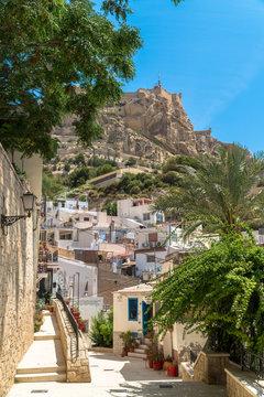 Alicante, Comunitat Valenciana / Spain - July 29th, 2019: Santa Cruz Neighborhood in the old city center with the Santa Barbara Castle in the distance