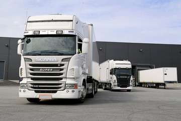 White Scania Trucks Ready to Unload at Warehouse. Illustrative Editorial content.