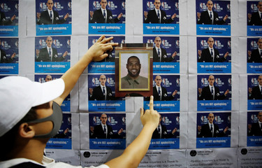 A protester puts NBA star LeBron James' photo on a wall during a gathering in support of NBA's Houston Rockets' team general manager Daryl Morey, who sent a tweet backing the pro-democracy movement, in Hong Kong