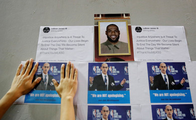 A protester puts a picture of Commissioner Adam Silver, next to NBA star LeBron James' photo, on a wall during a gathering in support of NBA's Houston Rockets' team general manager Daryl Morey, who sent a tweet backing the pro-democracy movement